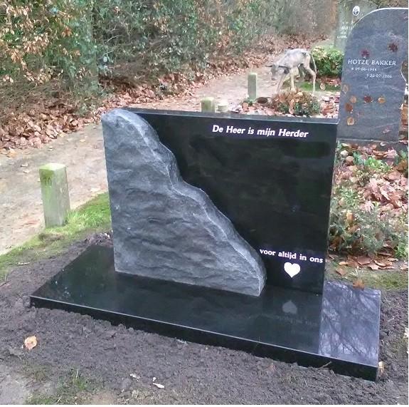 Zwart graniet grafmonument met ruw rotsachtig element